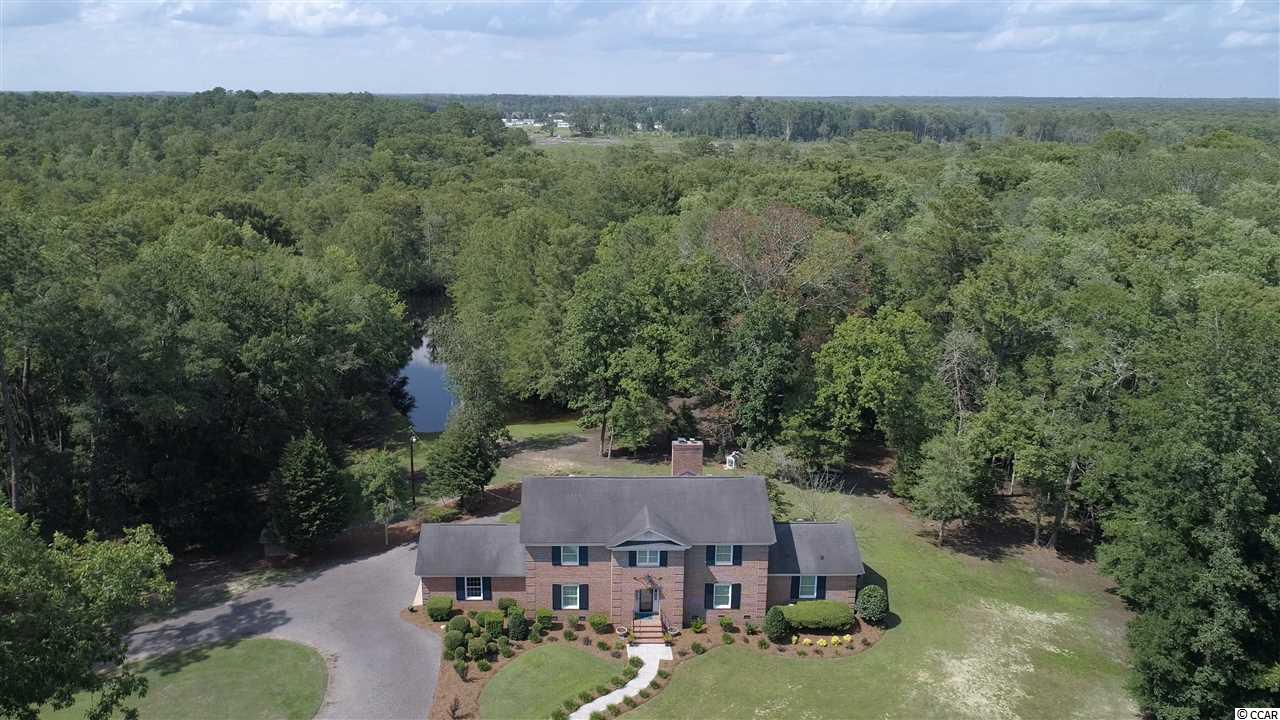 This is a rare find!  This magnificent home sits on 11.20 acres with 7 pecan trees and backs up to a deep water slough on the Waccamaw river.  The property offers lots of privacy. The Charm of this home is breathtaking, it has recently been remodeled,  all the electric and plumbing updated.  The kitchen features custom cabinetry, top of the line stainless steel appliances including the washer and dryer, double oven, granite counter tops and a walk in pantry.  There are 2 master suites great for mother-in-law quarters, owners suite has a custom closet that is to die for!  The spacious sun room located just off the kitchen has a great view of the river, there is an indoor grill and wall to wall windows, the custom hickory wood table located in the sun room conveys. The living and den area both have built-in and fireplaces, the fireplace in the den has a Hand hewn mantle and ceiling beams,  and custom fireplace insert, all doors are solid wood.  Other features include an office, tile and hardwood flooring,  laundry shoot, new 4 ton HVAC heat pump with new 1st level duct work and built in dehumidifier, home intercom system, whole home security camera system, new windows, new garage door.  There's also a utility shed with electric and new roof. Don't miss out on this one of a kind property.