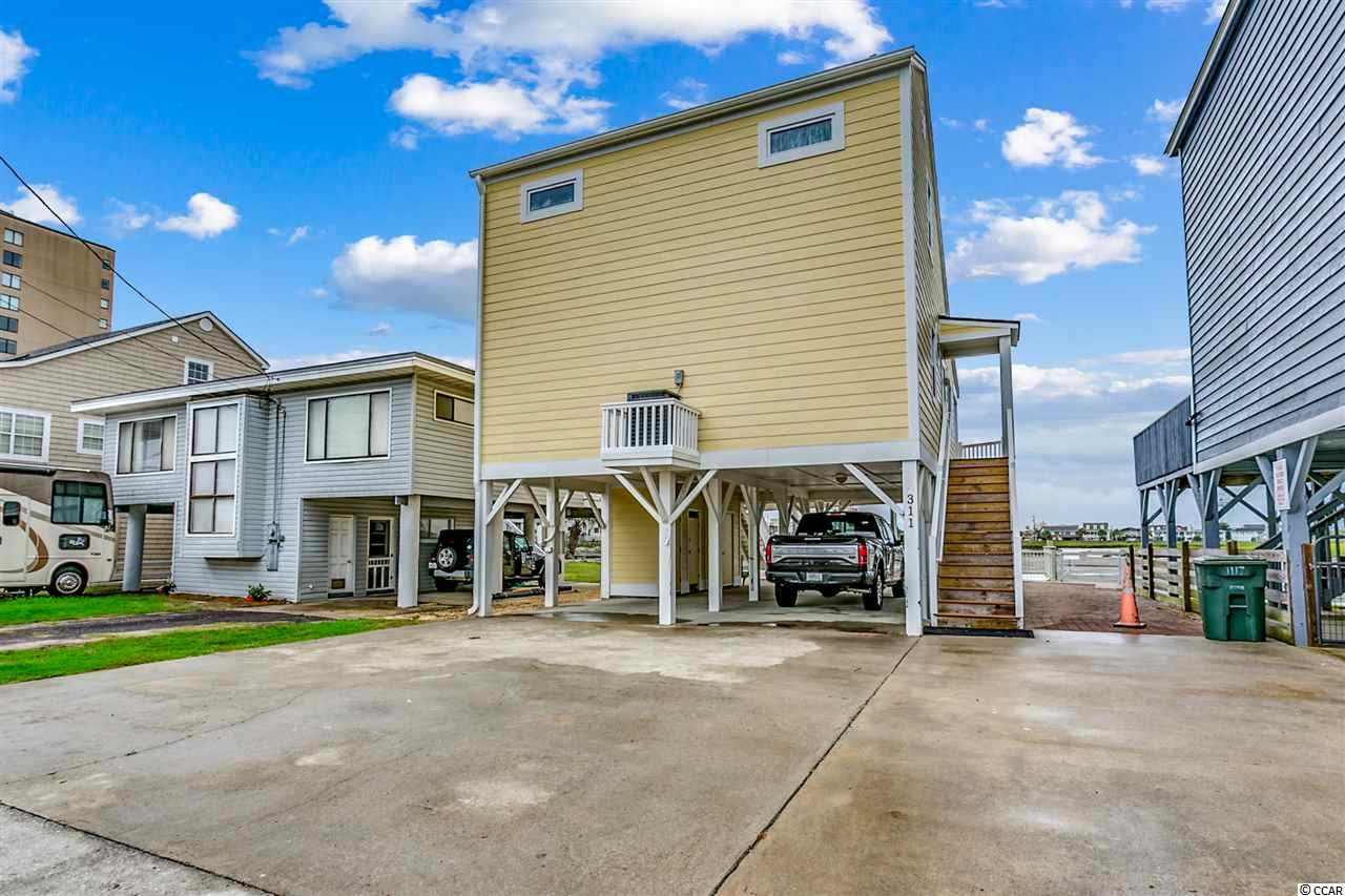 A RARE FIND -Beautiful home immaculately maintained selling furnished full of sunshine overlooking Hog Inlet off Lake Dr. on 42nd Ave. N. boasting a floating boat dock, new vinyl seawall with walking width concrete cap, 8000 lb. aluminum boat lift, aluminum ramp, fish cleaning station, composite deck & rails, pavers and amazingly awesome views of Hog Inlet and marsh and easy access to get your boat out to inlet waters and ocean. This beautiful home offers so many maintenance free features including Hardie plank color plus siding, all new windows and sliding glass door, new composite decking, two stairways from main level to ground level, gutters, handrails and an abundance of pavers.  Boasting an open, airy floor plan with vaulted ceiling in living room, the master bedroom can be found on main level with a private sink and vanity room leading to walk-in closet along with shared additional full bathroom allowing access from living area. Two guest bedrooms and full bathroom can be found upstairs.   Main living area and upstairs hall have had recently installed (2018) beautiful tile along with newly finished living room ceiling, new dishwasher and new flex AC lines to register.  Additional updates in 2017 include new hot water heater, kitchen range, and HVAC unit being replaced. Beautiful maintenance free composite decking on wrap around back porch and deck. This is truly a unique property and location with incredible water and sunset views with easy access to inlet waters and ocean with no dredging fee attached.  Treat yourself to an amazing experience!