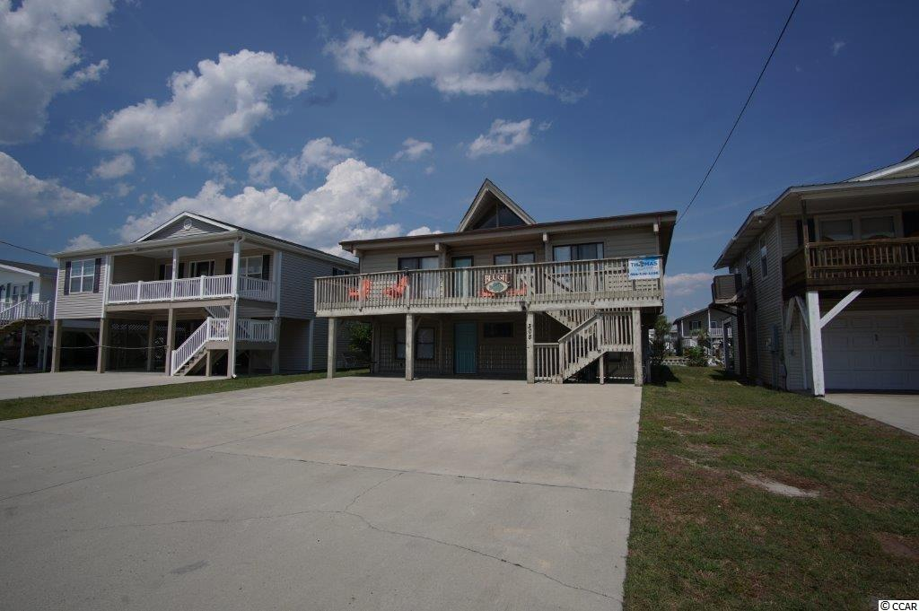 Bring the whole clan to enjoy this spacious 6 bedroom home on one of the Cherry Grove channels! Located on same street as community boat ramp where you can fish, kayak, picnic,etc & Heritage Preserve nearby.Just steps to the sparkling blue Atlantic Ocean with convenient public beach access located at beach end of 53rd Ave & across the boulevard to the strand. Home has 2 bedrooms & 2 baths & a bonus room on ground level. The main area of the house with the other 4 bedrooms,2 baths, large kitchen, dining, living room, large porches are accessible via an inside staircase as well as the exterior stairs.  Soaring cathedral ceiling in living room adds to the airy & beachy ambiance of this unique home.  Brings in great rental income if you decide to keep it on the existing rental program which has many repeat renters. Stationary dock on channel and ample parking for your vehicles. This is the well loved BluGil Channel house with character & charm reminiscent of the good old-time vintage channel houses! Two new exterior doors & new roof just installed!