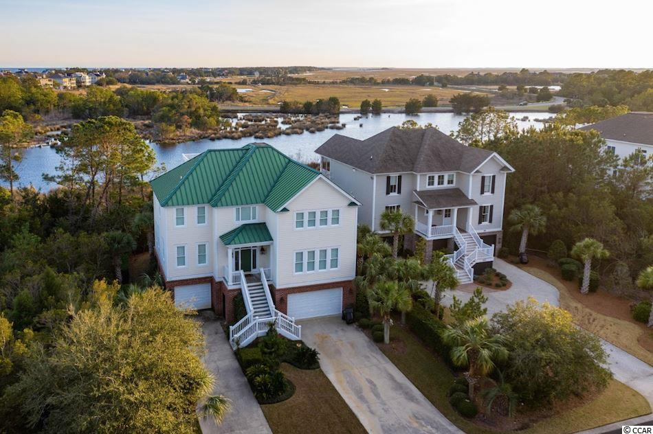 Enjoy easy access to the beach and capture the beautiful Beach House Pond and North Inlet Estuary marsh views all from 126 Permit Ct. in beautiful DeBordieu Colony.  This home has plenty of space for you and yours with 5 bedrooms and 5 ½ baths and provides a turn-key opportunity.  Enter through the front door or elevator on the first level and you will see four very spacious bedrooms and baths as well the large laundry/utility room and additional living area (could be an additional bedroom) for your guests.  Step outside to the screened porch to enjoy just one of the three outdoor living spaces this home provides.  On the second level you will find a great kitchen with breakfast bar seating that is wide open to the dining and living areas.  Enjoy libations from the wet bar adjacent to the kitchen!  The master bedroom and bath complete this level in addition to…another fabulous porch to take in the views.  Head up to the widow's walk above for the maximum view potential.  Complete with plantation shutters throughout and a keen eye for design, you could make this your new beach home today!  Debordieu is a private gated community. Being a member of the Debordieu Club provides members and guests with amenities of golf, tennis, boating, a fitness center, and multiple dining venues. Natural amenities include miles of beach and tidal creeks, walking trails and bike paths, and a delightful year round climate.