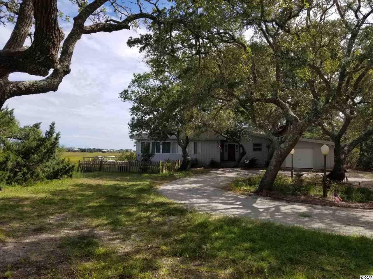 """Breathe in the salt marsh air and pluff mud and let the worries of the day wash away as you unwind on your back deck overlooking the gorgeous Midway creek and inlet, sipping a cool drink! Here's your unique opportunity to own a large, private peninsula surrounded by salt water, magnificent creek views, dock and swimming pool - there is simply no other property like this on the Grand Strand. Must see to appreciate this picturesque 1.21 acre property with majestic live oak trees and ample space to enjoy the Pawleys Island lifestyle. Once the family dream home of the iconic Louis Bryan """"Bumpy"""" Thompson of Pawleys Island, this 4-bedroom, 4-bath home, has been the site of many idyllic Pawleys Island family memories: parties, holidays, weddings, gatherings, and all-around fun. The home boasts an incredible deck and pool area with creek access and amazing views of the creek and inlet. The inside features large, open rooms, a huge sunken great room, perfect for family gatherings with a gorgeous large mantlepiece, a cozy """"movie room,"""" and an open concept kitchen and dining room. There are three large bedrooms in the main house, and a fourth bedroom in the attached mother-in-law suite. The suite features a large bedroom and bathroom, living room, and efficiency kitchen and can be closed off from the rest of the house – perfect for potential rental income. The home could use some TLC, but has amazing potential on one of the most unique lots in the area. Being here feels like your own private island – yet still just a short drive from all the best the Lowcountry has to offer. This wonderful Midway Creek property is conveniently located to Brookgreen Gardens and Litchfield Beaches, Pawleys Island and Huntington Beach State Park, restaurants, shopping, art galleries and medical facilities. There are also many world class golf courses in the Pawleys Island area. Come, relax, and play in the sun at Pawleys Island, South Carolina! Pawleys Island is centrally located to everything yo"""