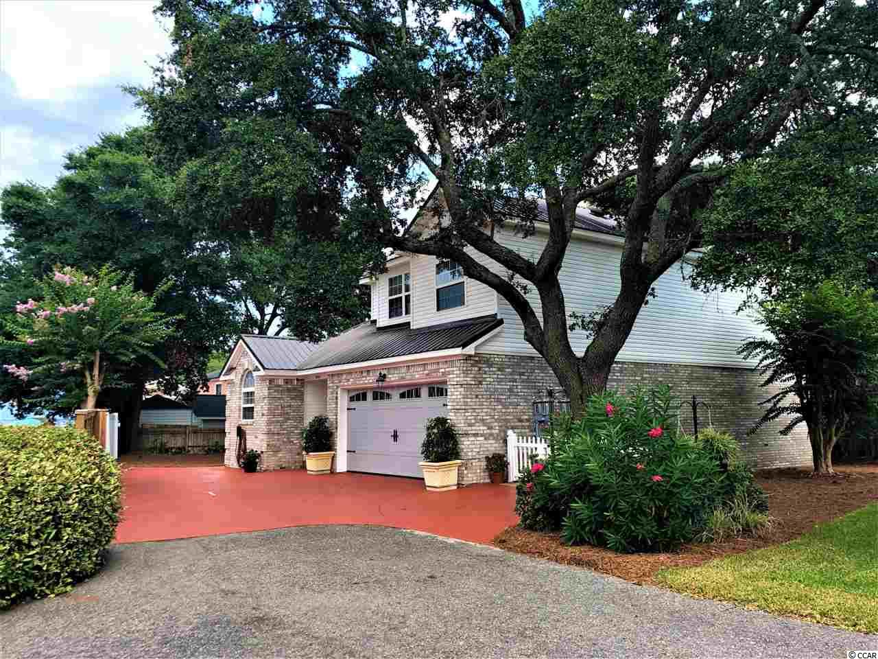 """Windy Hill - A """"Hidden Gem"""", """"Absolutely Gorgeous"""" and """"Meticulously Maintained"""" is this 4 BR, 3 1/2 BA home, 2 car garage, nestled among live oaks on a quiet private street, in the very desirable area of """"Windy Hill"""" in North Myrtle Beach.  NO HOA fees, low maintenance Brick/Vinyl Siding and less than 500 Ft to Ocean Blvd, one is pressed to find anything like it near the beach.  This home is """"like new"""" with """"Major Renovations"""", all New in 2018:  All New (HVAC with NEST smart thermostat, Metal Roof, Outside Storage Bldg, Screened Porch, Bricked Patio, Hurricane Garage door, Utility Room in Garage, new Tile Flooring in Garage, Interior painted throughout, New Ceramic Tile throughout, Carpet in Bedrooms, Downstairs Half-Bath remodeled, Granite Counters in Kitchen, New Whirlpool Kitchen Appliances: Double Oven, MWO, DW, Refrigerator, New Kitchen sink, Gas Logs and Firebox in Living Room, new Light Fixtures, new Ceiling Fans, Murphy Bed in 4th upstairs bedroom, new Easy-Clean Toilets, new Window Blinds, Paved Golf Cart parking and Picket Fence added in front of home)!  New Water Heater in 2017!      What a quiet private setting for entertaining on your screened back porch. The home features an Open and Flowing Floorplan with Gas logged FP, Large Master Bedroom on First Floor, and Laundry room off Master Bath.  THIS HOME IS A MUST SEE!  DON'T LET THIS ONE GET AWAY!  TOO MUCH TO OFFER!  YOU WILL LOVE IT!"""