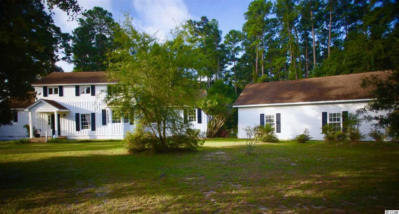 "Welcome home to this one of a kind property with plenty of land and easy access to all Myrtle Beach has to offer. Thanks to the new International Dr extension, which is an 1/8th of a mile away, you can now be at the beach in 10 minutes! This 3 bedroom 2.5 bath home is nestled on a large 1.12 acre corner lot in Chelsey Lakes, a 26 home private ""No HOA"" community with river access— to 20 acres of preserved land that can be used to camp, fish, kayak, jet ski, launch a boat, or take a nature walk to relax. A 4-bay garage with a 10-foot ceiling and central heating and cooling can be used as a workshop, studio and to store all your boats, rvs, jet skis, and toys. When it comes to privacy this home has plenty! It is surrounded by lush foliage that offers a natural barrier from the surrounding properties.  Plus, the adjacent lot is a green space which cannot be built on. When not enjoying the beautiful, spacious and gracious interior of the home, you can move family get togethers outside onto the deck or Stone patio. Roast marshmallows under the stars in the brick pergola with built-in fireplace and BBQ. So, if you like the idea of living in an ultra-private community with no HOA and away from all the hustle and bustle of the beach, yet still a short drive to it all, then schedule your showing today."