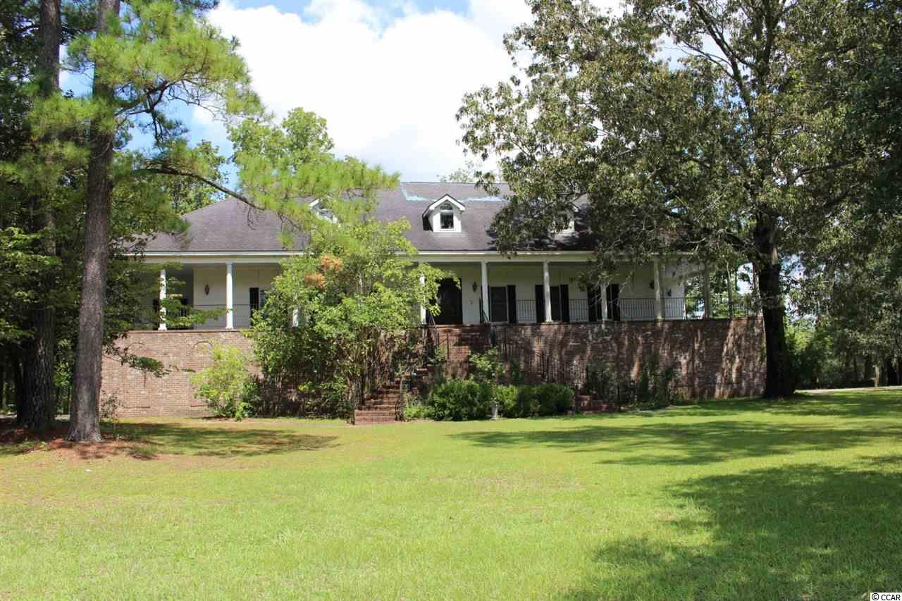 What a beautiful location right on the Waccamaw River.  Sitting high on the bank and a large three story home with over 8,000 square feet of space.  Tons of potential and wonderful opportunities for you to make this a magnificent estate for yourself.   Wrap around porch for those cool autumn evenings!!  The main floor (Second Story)  boasts a large kitchen with commercial appliances and space galore.  Along with the living room, there is a separate large sweeping sun room overlooking the river and the land.  WOW!!  In addition there are three large bedrooms, formal dining room and 2.5 bathrooms.  The top floor boasts of two large bedrooms, a full bath and tons of storage along with wonderful nooks and crannies to explore.  The ground floor has the Garage and separate living quarters that has room for 12+ cars, toys, storage rooms, the list goes on and on.  Plus that garage area also has a kitchen, small dining area, full bath and living/sleeping area.  There is an elevator in the home going to all three floors (needs work does not run currently)  There is a river house, walkway and gazebo that, while needs repairs, will be quite lovely when properly returned to it's graceful beauty.  This is a MUST SEE HOME.  The seller will not allow it to be shown unless the person requesting showing has proof of funds or adequate preapproval letter from qualified lender.  Ask your agent for further information on lender and property.  You will be amazed at this beauty's potential!