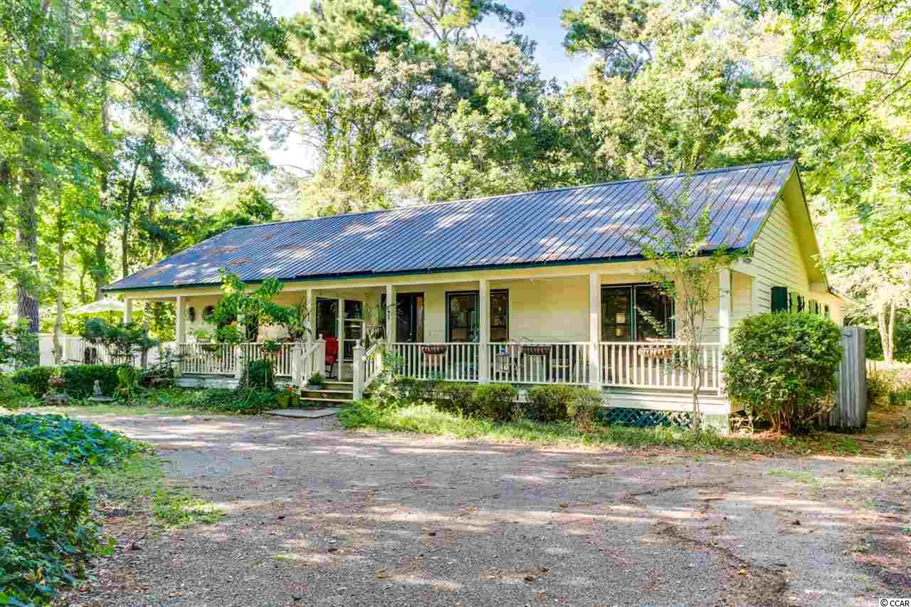 This is the dream home for the owner who wants privacy as well as a lot of character!  This charming home is located on a cul de sac in a quiet neighborhood; the lot is deep and backs to a nature Preserve and Heritage Plantation.  You can park your boat on this very large lot after you return from the Hagley boat landing which is only a minutes drive.  Home is well cared fo. Great hardwood floors and woodwork, newer windows.  Another great feature are the wide hallways, it is Handicap accessible.  Attached to the house is a fifth bedroom or studio or office with its own bath.   Outside living is sure to please including a patio with a fire pit, a huge deck and large greenhouse 12 x 22 often used for social gatherings.  The front porch is for lazy days relaxing and just enjoying the natural surroundings or for evenings enjoying your favorite beverage by candle light.  Mature landscaping surrounds the home and the circular driveway makes for an easy entry and exit.  The Outside shower is a much needed feature as for your guests to rinse off the sand after a day at the Pawleys Island beach which is only a 10 minute drive.  The lawn well is a cost saving feature you are sure to appreciate   when your water bill comes.  The Exterior is newly painted. and the Heating and air is approximately  one year old.  All of this at a very affordable price!!!  Take advantage of this buyers market and this amazing piece of property!  Call today for a private showing.