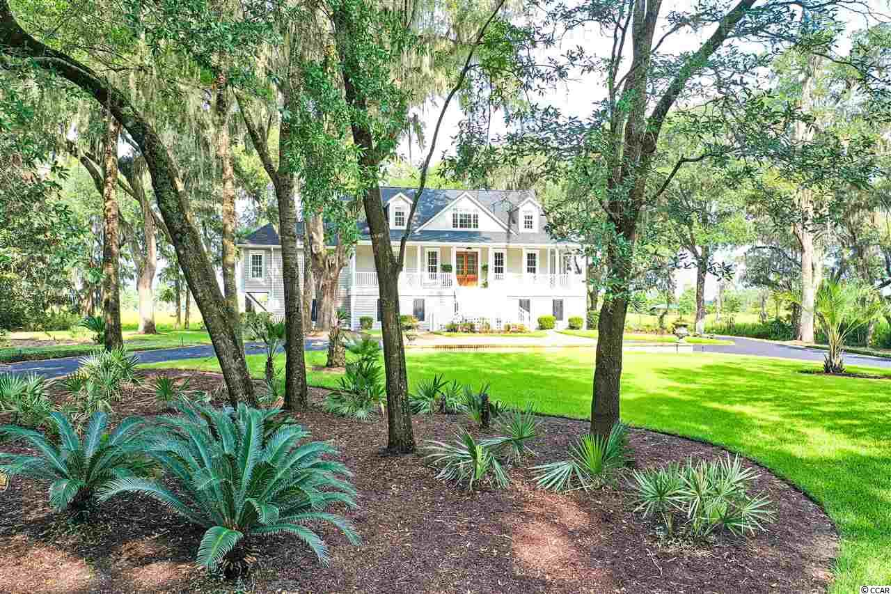 Amazing views of historic ricefields out to the Intracoastal Waterway/Waccamaw River from this beautiful lowcountry home on 8.6 acres in River Oaks of Pawleys Island.  Totally updated over the past 2 years and has a private creek dock leading out to the river!  The back of the home has floor to ceiling windows to ensure you never miss a majestic sunset. This charming estate home is adorned with moss draped live oaks and a private back yard with dock leading out for a day on the boat in the Intracoastal Waterway.  Enter into the foyer from the large front porch and look straight out to the beautiful Waccamaw River.  Heart pine flooring throughout the main level and shiplap walls provide warmth and character in this relaxing home.  No details were spared in this updated home!  Enjoy a cool drink with family and friends in the bright and spacious sunroom while watching the boats go up and down the waterway.  The gracious kitchen features custom cabinets, built-in oven, gas range, 2 sinks, stainless steel appliances, granite and stainless counter tops and more!  Large master suite has double glass doors that open unto a large screen porch and has his and her bathroom areas with separate water closets, free standing tub and large walk in shower!  The upstairs has two bedrooms with bathrooms and a loft area that would be a perfect office or playroom!  Need a mother-in-law or guest suite?  On the bottom floor is a full apartment complete with a kitchen, living room, bedroom, laundry and bathroom...completely updated!  Another downstairs feature is a separate home office with views out to the waterway.  Other features to be sure not to overlook include an elevator, automatic roll up screen on sunroom windows, outdoor firepit and more!  The landscaping is impeccably maintained and full of beautiful old live oaks!  Enjoy riverfront living at its finest in this move in ready estate!