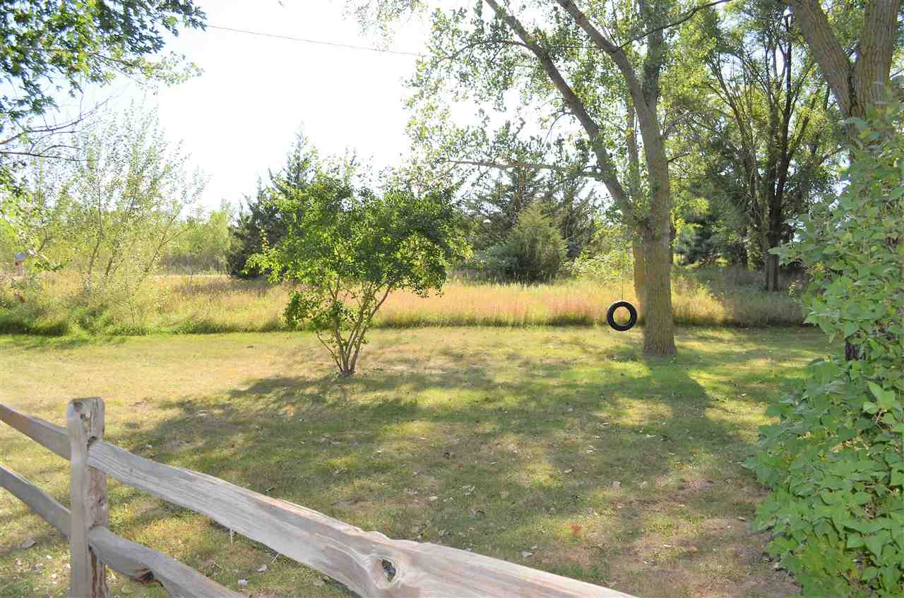 If you're looking for space to roam and a feeling of seclusion, then this is the acreage for you! Surrounded by trees, you nearly don't see this one from the road.  Sitting on 4.61 acres, this 4 Br, 2 bath home is seeking a new family to love!  Enjoy the manmade pond and grow your own food in the established garden area.  The 2+ car garage includes an office area and 2 side rooms perfect for workshop/crafting area or additional storage.  The Master Bedroom offers a full Master Bath and double closets! The insulated metal roof was just put on in 2018.  Enjoy the cozy country kitchen with walk in pantry. Set outside and enjoy the evenings in the screened in front porch/patio!  Don't let this one get away!!  **International M Tractor is included with personal property.