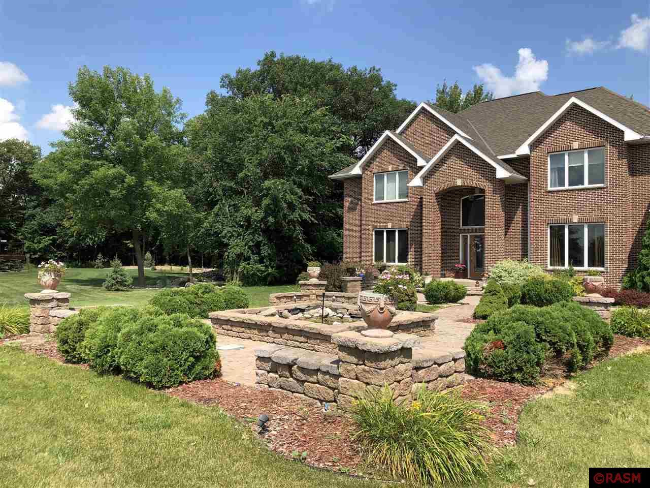 This two-story, quality-constructed, custom brick home offers great space for any lifestyle. Home features beautiful hardwood floors, architectural details and stunning stonework on three gas fireplaces.  An eat-in kitchen is featured along with separate space for formal dining.  Master bedroom with private on-suite bath.  Three additional bedrooms, laundry room and office on upper level. Lower level includes great room, entertainment space with wet-bar, bedroom, bath and office.  Three stall attached garage is heated and sheet-rocked.  Four season porch with access to maintenance free deck with private backyard. Feels like country living. One acre lot with stone fountain and beautiful landscaping.